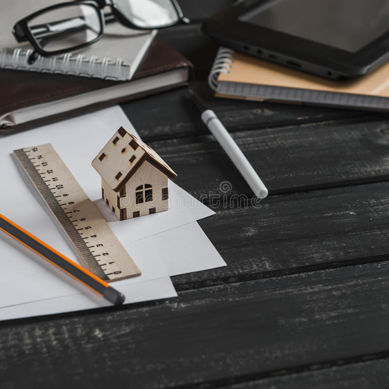 Planläggning av konstruktionen av ett hus Kontorsskrivbord med affärsobjekt - den öppna anteckningsboken, minnestavladatoren, exp fotografering för bildbyråer