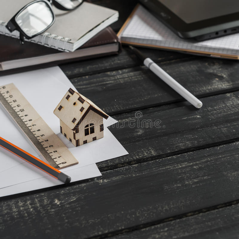 Planläggning av konstruktionen av ett hus Kontorsskrivbord med affärsobjekt - den öppna anteckningsboken, minnestavladatoren, exp royaltyfri bild