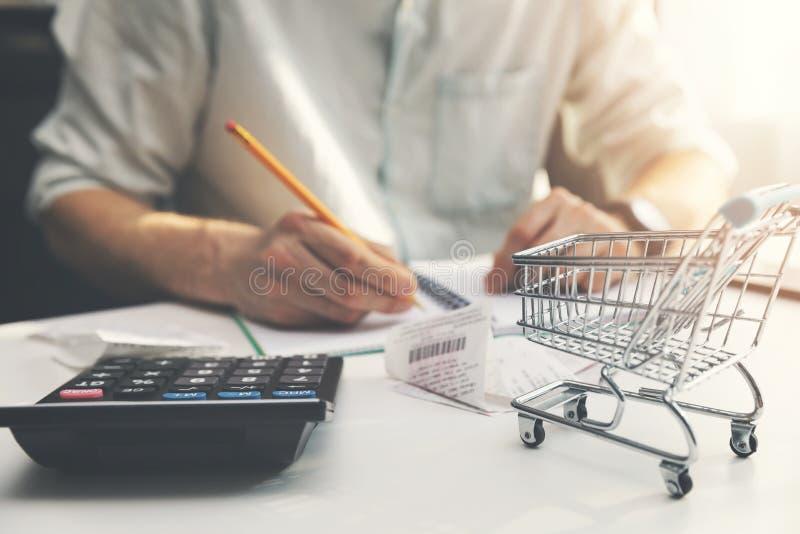 Planläggning för familjbudget - man som räknar och kontrollerar dagliga kostnader för hushåll arkivbilder