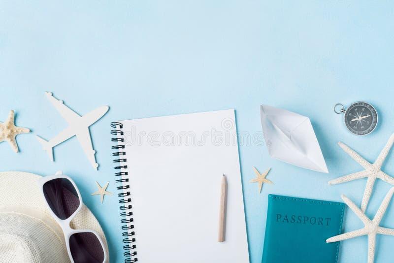 Planläggningssommarferier, turism och turtappningbakgrund Handelsresandeanteckningsbok med tourizmtillbehör på blå skrivbords- si royaltyfria bilder