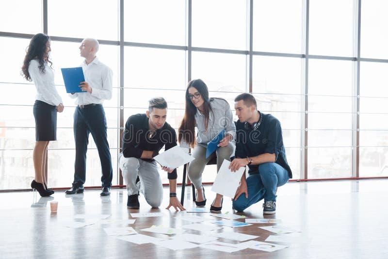 Planläggningsstrategi tillsammans Affärslag som ser legitimationshandlingar på golv med chefen som pekar till en idé samarbete arkivfoton