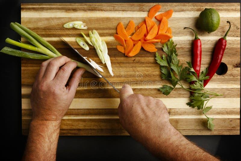 Planmening van handen die een verscheidenheid van groenten hakken royalty-vrije stock foto's
