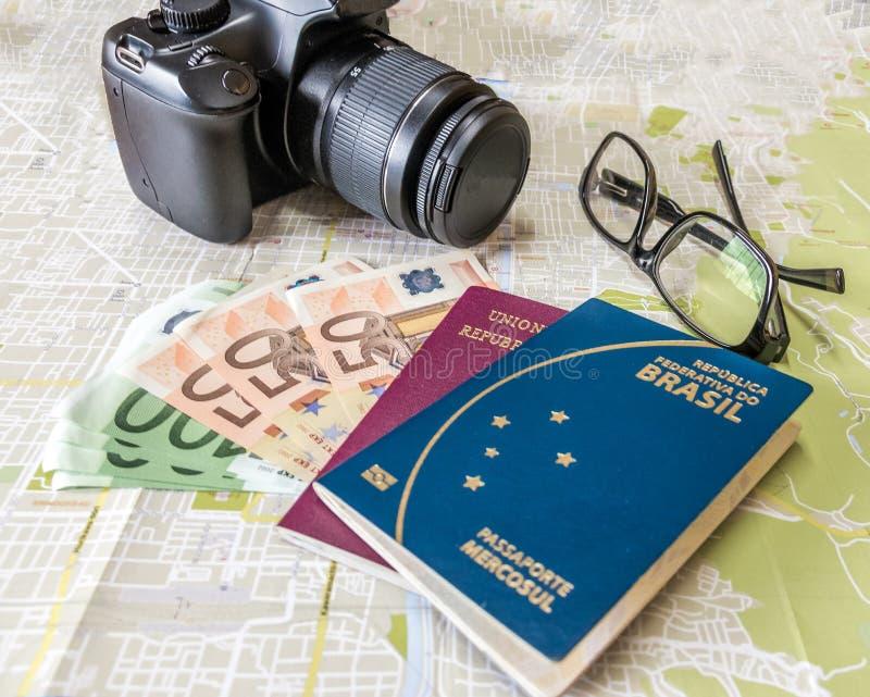 Plannend een reis - Braziliaanse en Italiaanse paspoorten op stadskaart met euro rekeningengeld, camera en glazen stock foto's