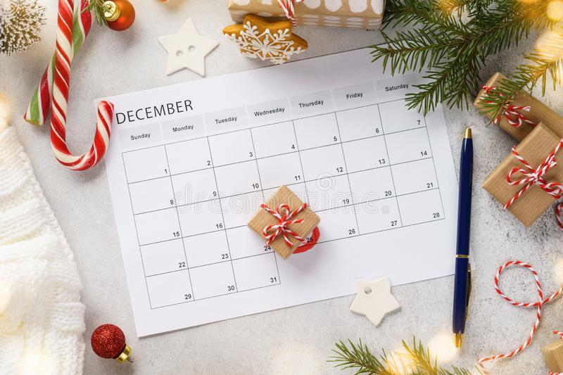 Planner page with Christmas gift box lying on 25th of December. Xmas decoration and sweets around. Holidays preparation, calendar, marked, date, background royalty free stock photography