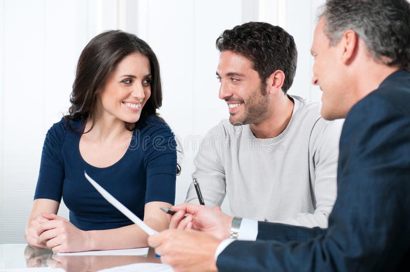 Planning bank investments. Financial consultant presents bank investments to a young couple royalty free stock image