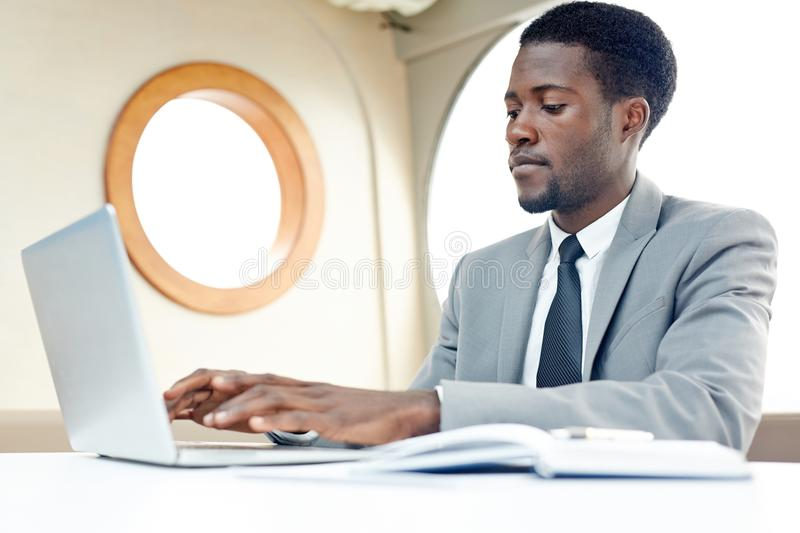 Planning on business travel. African-american specialist typing on laptop inside steamship and organizing work stock images
