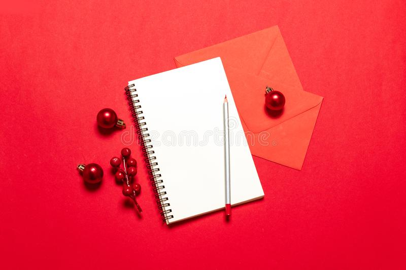 Planning concept. Top view goals list with notebook,pen, christmas balls, mail card on red desk royalty free stock image