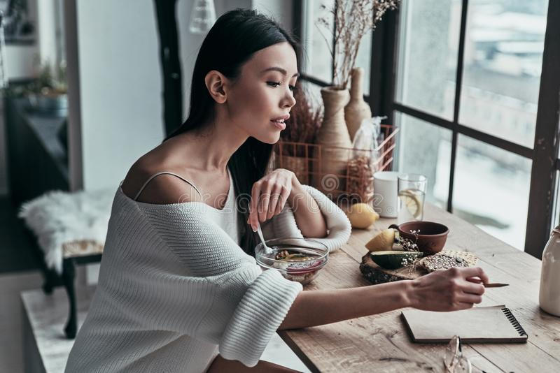 Planning the day. Attractive young woman eating healthy breakfast and writing something down while sitting near the window at home royalty free stock photo