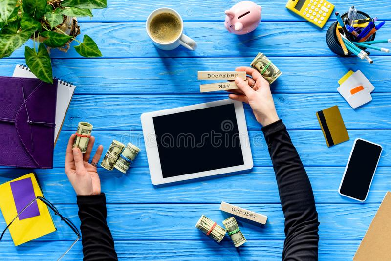 Planning expenses concept with business person holding calendar and money on blue wooden table royalty free stock image