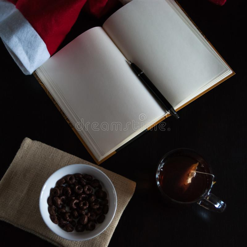 Planning future on Christmas: a notebook with blank pages, a black pen, Santa hat, glass mug with teabag, white bowl of chocolate. Cereal rings and milk on stock photo