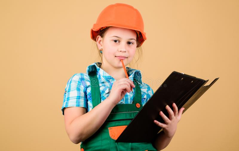 Planning her week. Builder engineer architect. Kid worker in hard hat. Child care development. Foreman inspector. Repair. Small girl repairing in workshop royalty free stock photography
