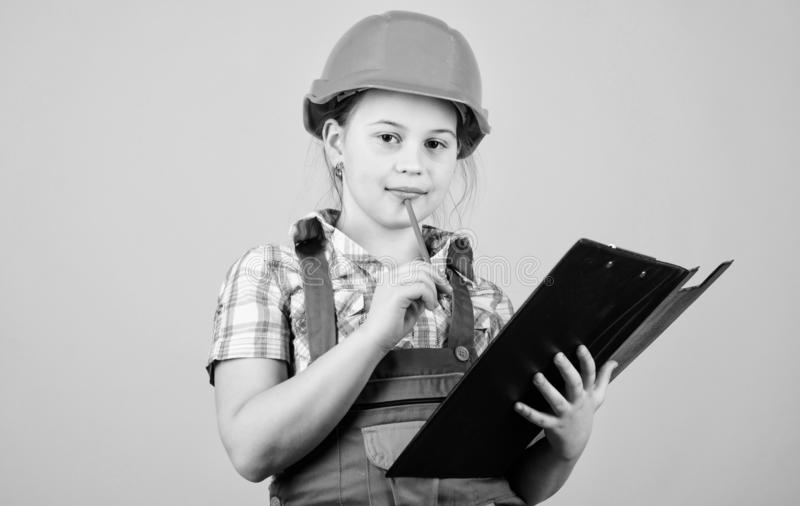 Planning her week. Builder engineer architect. Kid worker in hard hat. Child care development. Foreman inspector. Repair. Small girl repairing in workshop stock photography