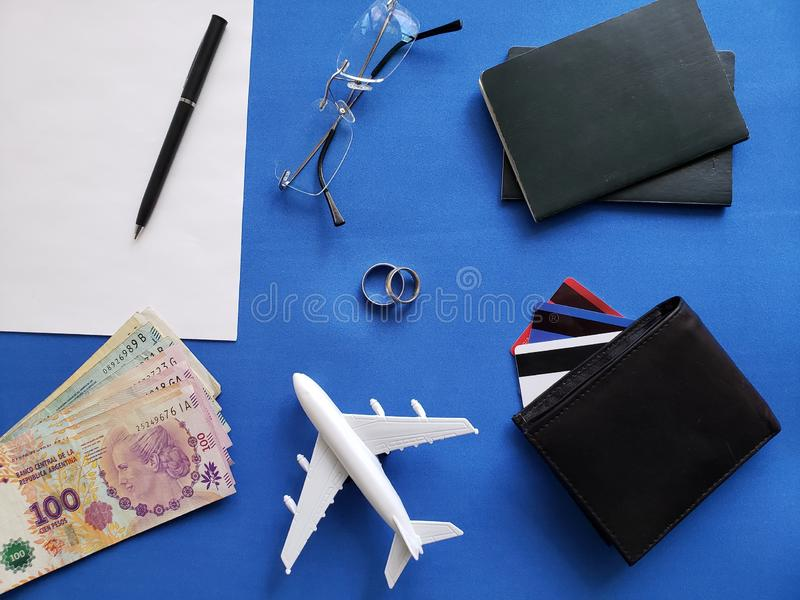 planning the honeymoon trip, rings, eyeglasses, argentine banknotes, passports, credit cards and figure of an airplane, top view royalty free stock image