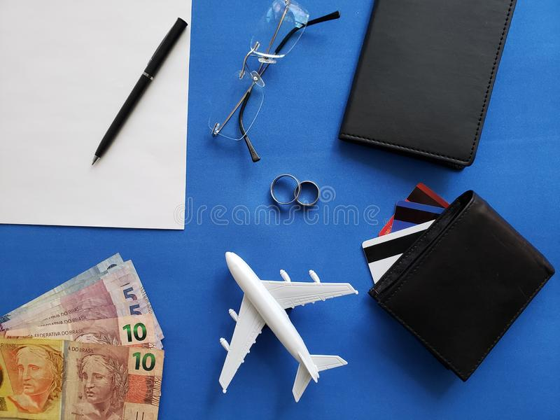 planning the honeymoon trip, rings, eyeglasses, brazilian banknotes, passports, credit cards and figure of an airplane, top view stock photos