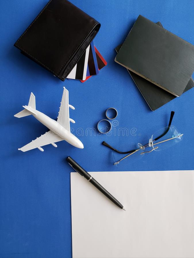 planning the honeymoon trip, rings, eyeglasses, passports, credit cards and figure of an airplane, view from above royalty free stock images