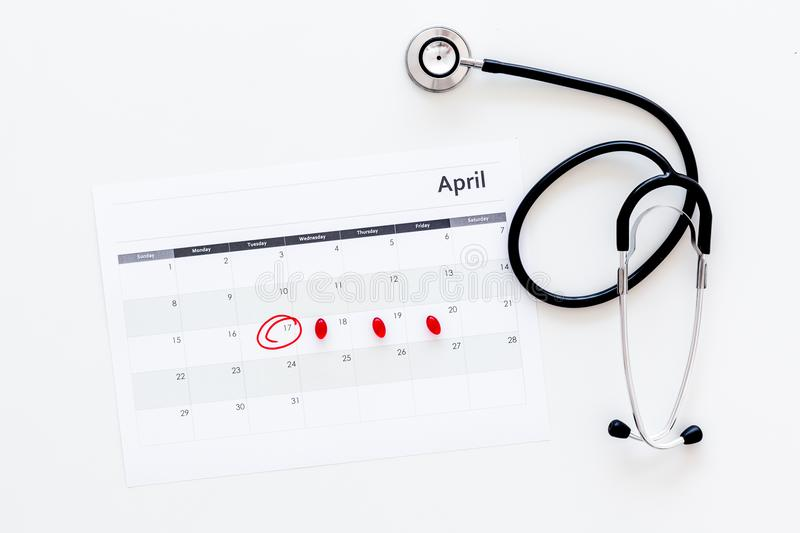 Planning medical examination concept. Regular medical examinations. Calendar with date circled, pills and stethoscope on stock image