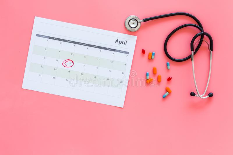 Planning medical examination concept. Regular medical examinations. Calendar with date circled, pills and stethoscope on stock photography
