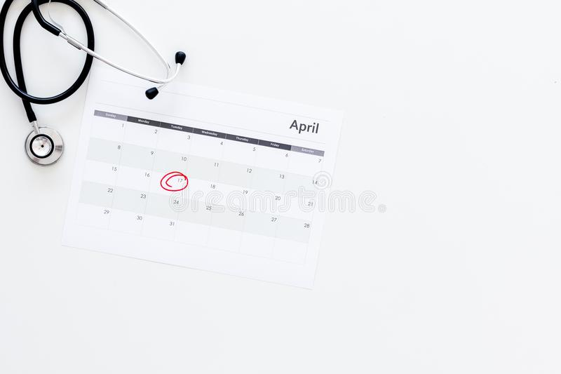 Planning medical examination concept. Regular medical examinations. Calendar with date circled and stethoscope on white. Background top view royalty free stock photography