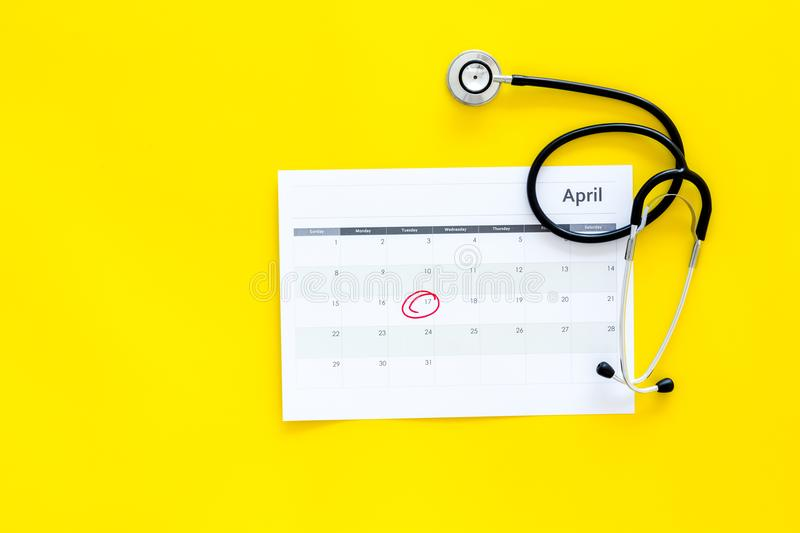 Planning medical examination concept. Regular medical examinations. Calendar with date circled and stethoscope on yellow stock photo