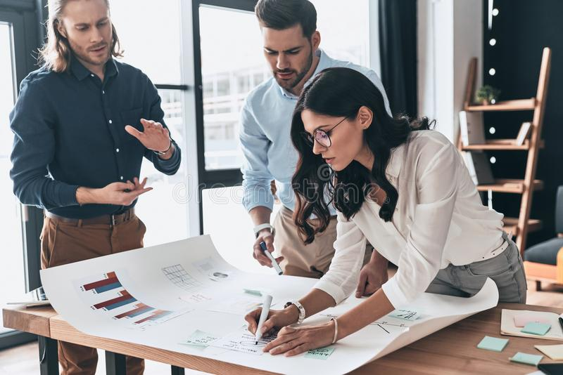 Planning new business strategy. Group of young confident business people discussing something while woman writing on blueprint in. Planning new business strategy stock photo