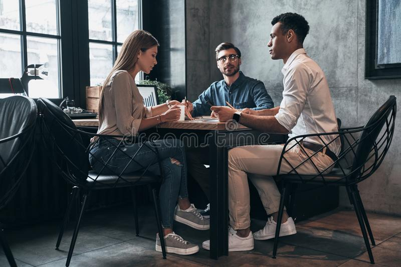 Planning new business strategy. Group of young confident people stock images