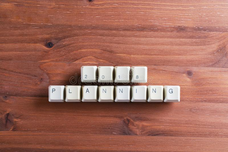 Planning 2018 new year on computer keyboard keys buttons on wood. Planning 2018 new year. Flat lay view from above on the table with computer keyboard keys stock photography