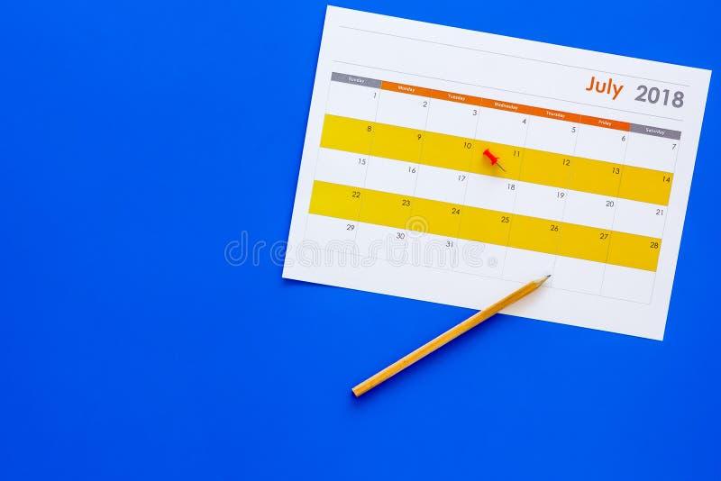 planning Richt de datum in kalender door punaise Bepaal de doelstelling Kies datum Kalender op blauw achtergrond hoogste meningse royalty-vrije stock foto's