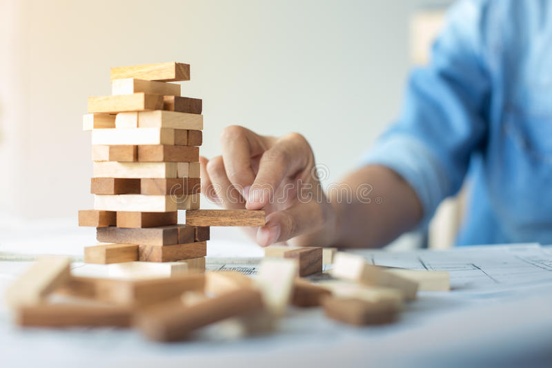 Planning, risk and strategy in business, businessman and engineer gambling placing wooden block on a tower. stock image