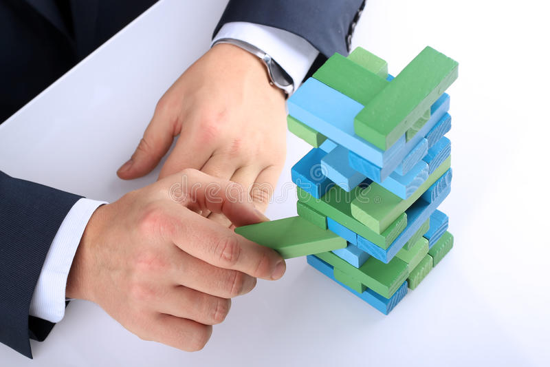Planning, risk and strategy in business, businessman getting out a wooden block from a tower royalty free stock photography