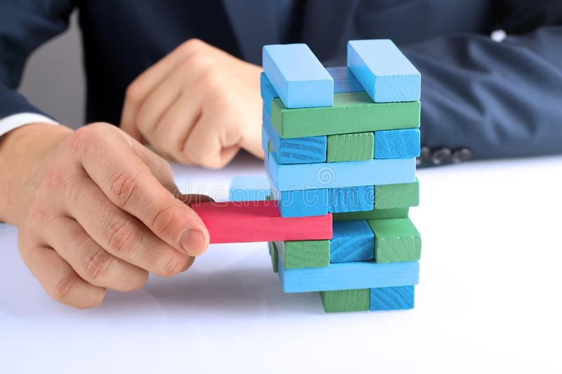 Planning, risk and strategy in business, businessman getting out a wooden block from a tower royalty free stock photos