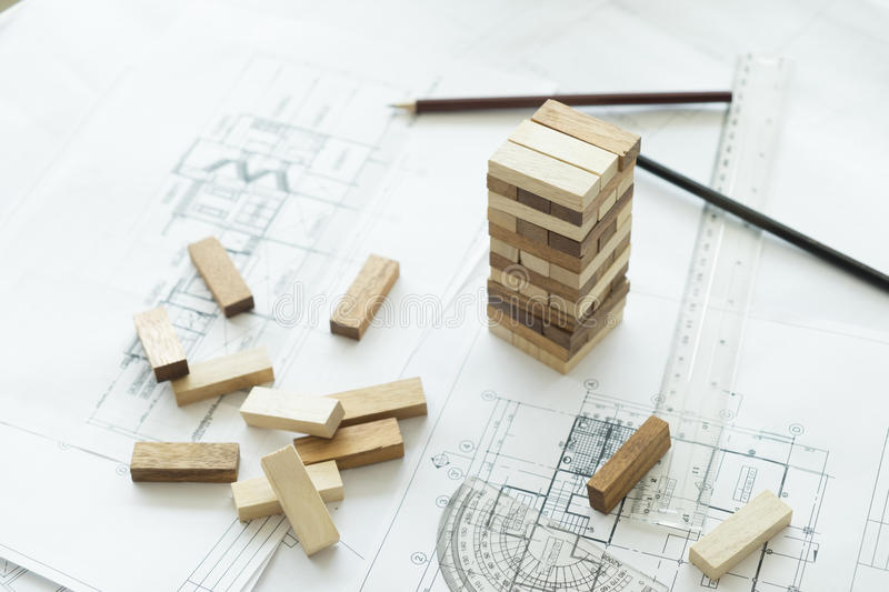 Planning, risk and strategy of project management in business. Businessman and engineer gambling placing wooden block on a tower.Business and construction royalty free stock image