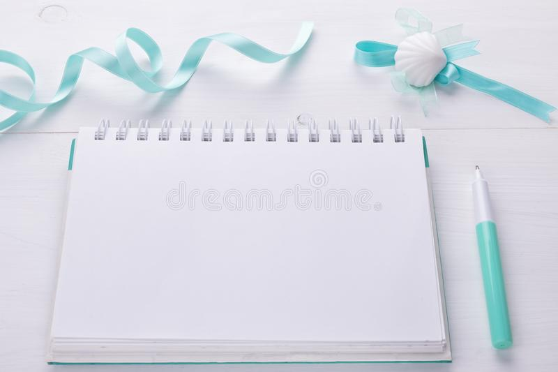 Planning still life of fashion woman, objects on white: emply notepade and pen and cozy mint ribbon stock photography