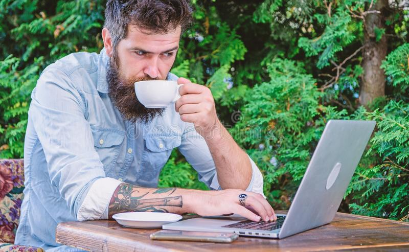 Planning vacation. Book apartment online. Man bearded hipster sit outdoors with laptop surfing internet and drinking. Coffee. Guy looking for apartment. Find royalty free stock photography