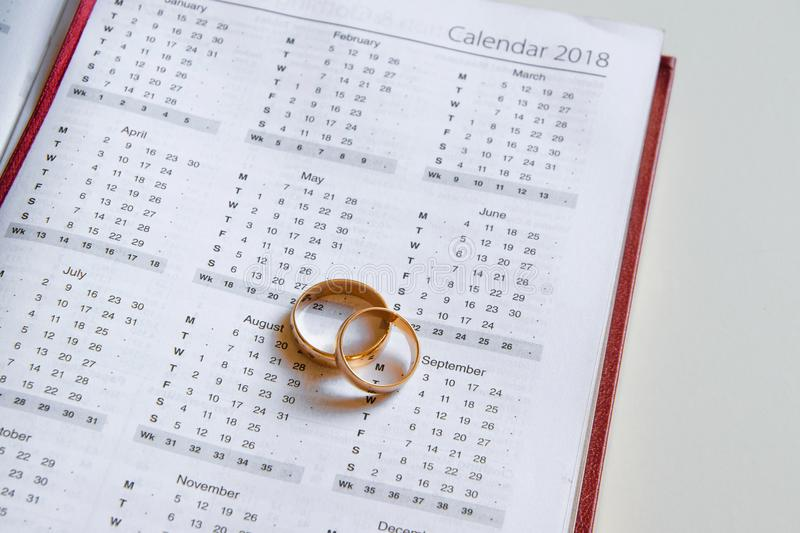 Planning a wedding in 2018. Calendar of 2018 and two wedding rings and on white background stock photos