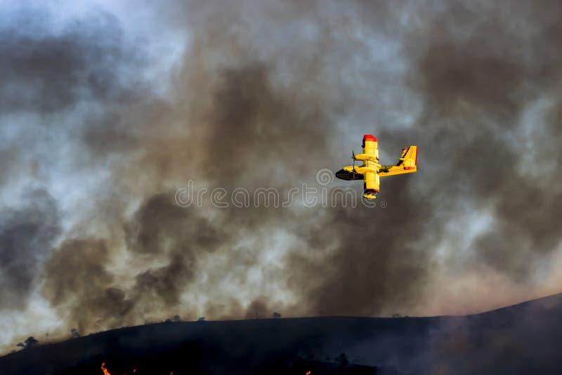 Plano amarelo brilhante voa através do céu fumarento durante o fogo de Califórnia imagens de stock royalty free