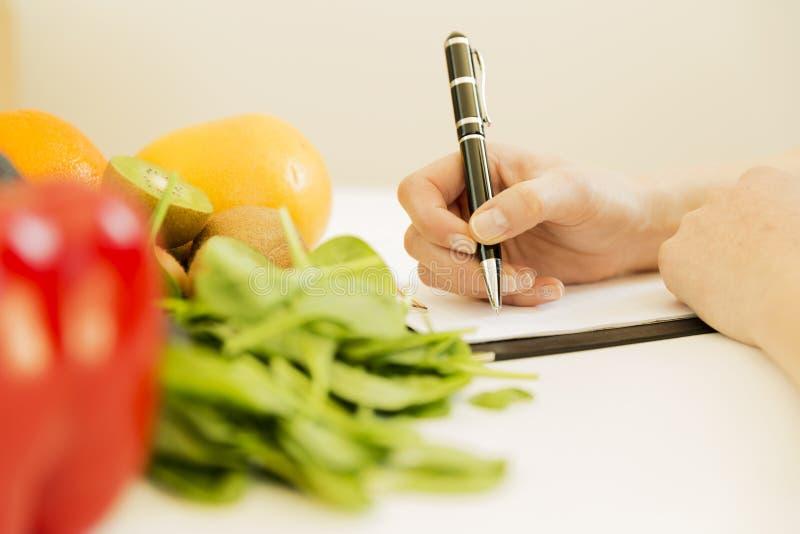 Plano da dieta da escrita da mulher do nutricionista na tabela completamente dos frutos e fotos de stock