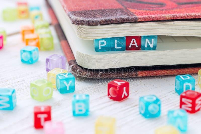 PLANO da palavra escrito em um bloco colorido em um livro imagem de stock