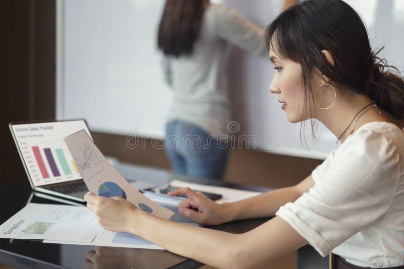 Plano de funcionamento incorporado, asiático focalizado sério da mulher de negócios com vista de documentos para tentar ao proble fotos de stock royalty free