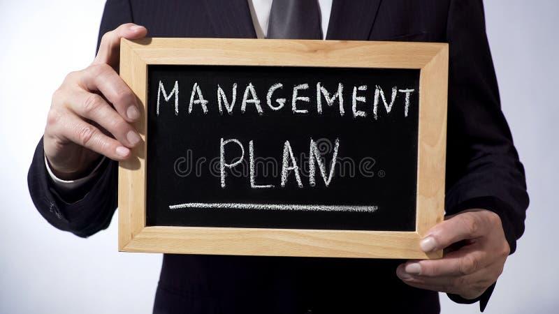 Plano de gestão redigido no quadro-negro, pessoa do negócio que guarda o sinal, estratégia imagens de stock