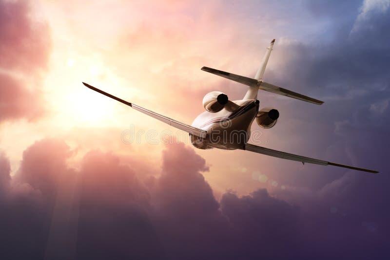 Plano de jato privado no céu no por do sol fotos de stock royalty free