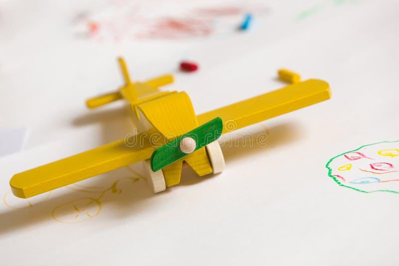 Plano de juguete de madera amarilla sobre fondo blanco Educación, niños, concepto de juego Dibujos para niños con juguete Infanci fotos de archivo libres de regalías