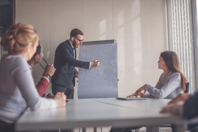 Plano de negócios explicado no flipchart pelo CEO aos empregados imagem de stock royalty free