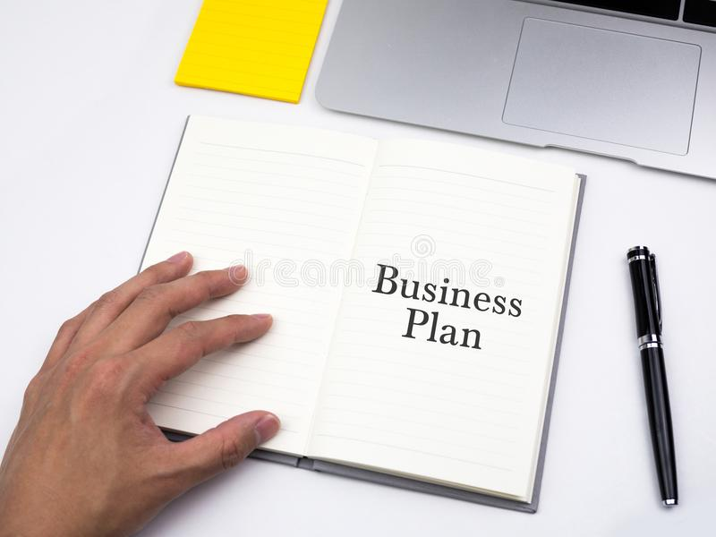 Plano de negócios redigido no caderno aberto na mesa do trabalho imagem de stock royalty free