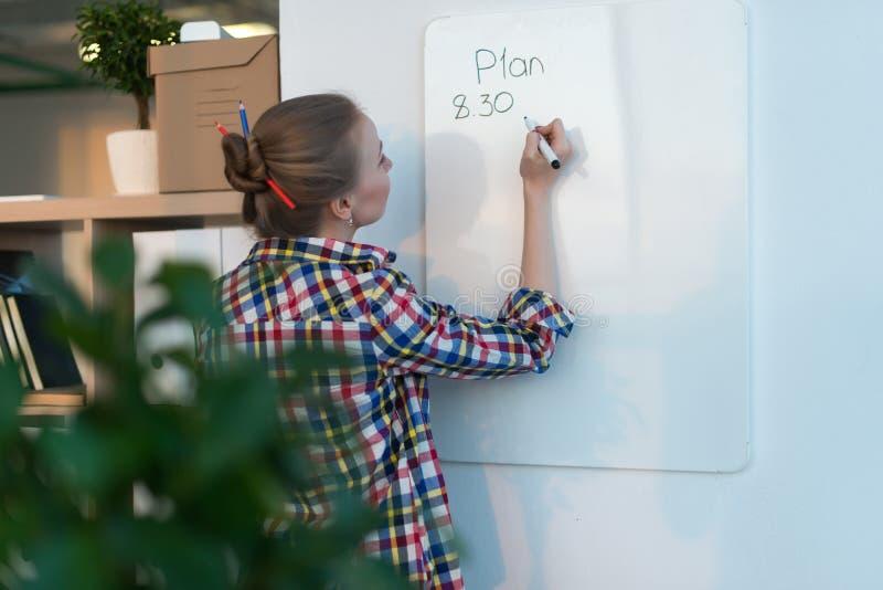 Plano do dia da escrita da jovem mulher na placa branca, marcador da terra arrendada no assistente Retrato da opinião traseira da foto de stock royalty free