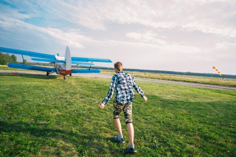 Plano e criança O menino está correndo atrás de decolar o plano na clareira verde foto de stock royalty free