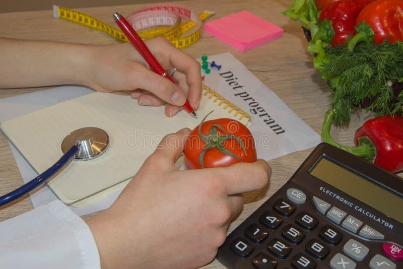 Plano fêmea da dieta da escrita da mão do nutricionista no caderno contra a composição do legume fresco Propaganda da nutrição da fotografia de stock