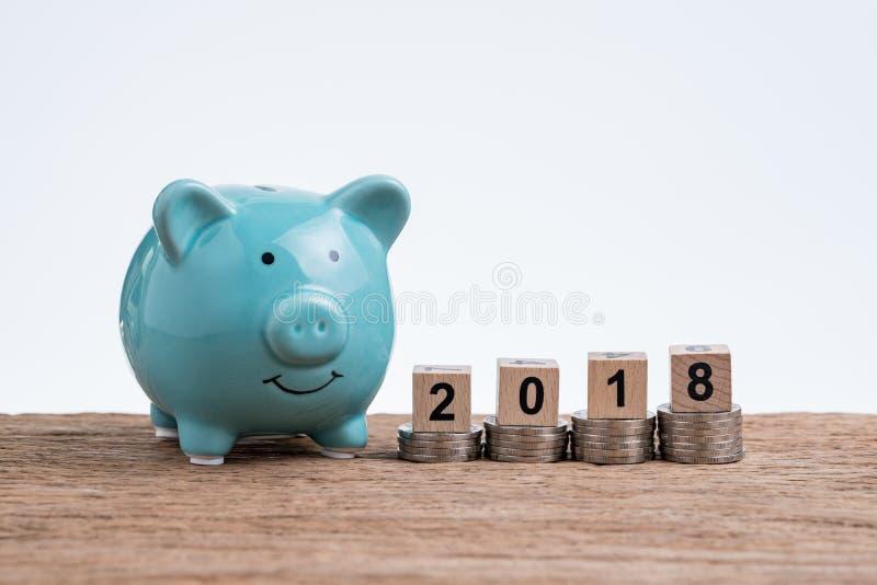 Plano financeiro do ano 2018 com o mealheiro e as moedas empilhados sobre a fotos de stock royalty free