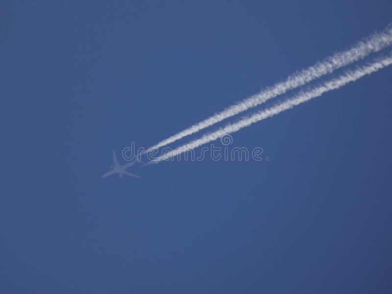 Plano sulcando o céu azul e deixando uma vigília branca imagem de stock royalty free
