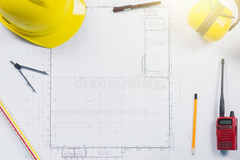 Planos da construção com capacete e o desenho amarelos fotografia de stock