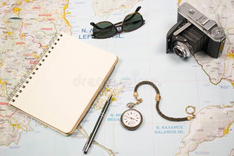 Planos de curso com o mapa da ilha Grécia e dos objetos A câmera, vidros de sol pocket o relógio e o caderno imagem de stock royalty free